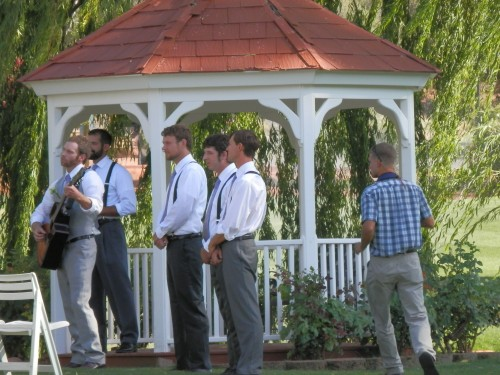 Adam Plays Guitar as Groomsmen Watch the Bridal Party Approaching