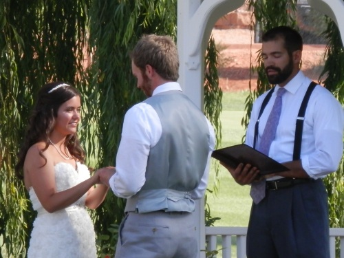 Cassidy and Adam Saying their Vows as Officiant Marc Maclean Watches On