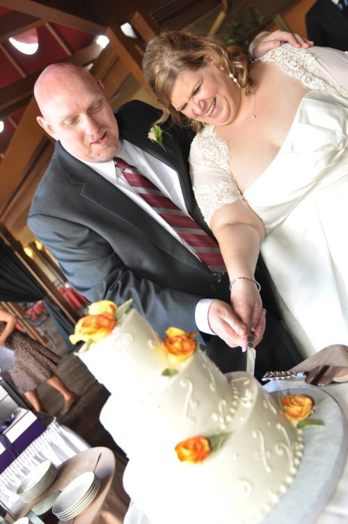 Paul and Michelle cutting their wedding cake - Photo by Amy Ijams.